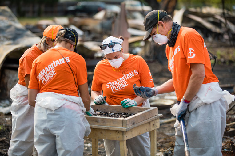 Volunteers pick meticulously through the ashes at Jackson County properties.