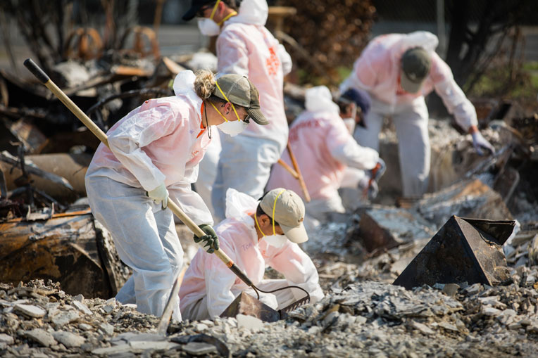 They wear protective suits, masks, and gloves as they shovel and sort through the ashes.