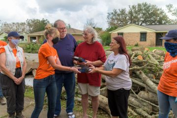 Volunteers present a Bible to Laurie Romani (right) and Marilyn and Steve Hobbs.