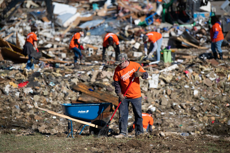 Volunteers near Nashville Tennessee clean up a devastated yard after tornado ripped through the area in early 2020.