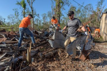 Edward Graham and John Pryor, left, join Team Patriot volunteers in picking through the rubble near a home in Louisiana.