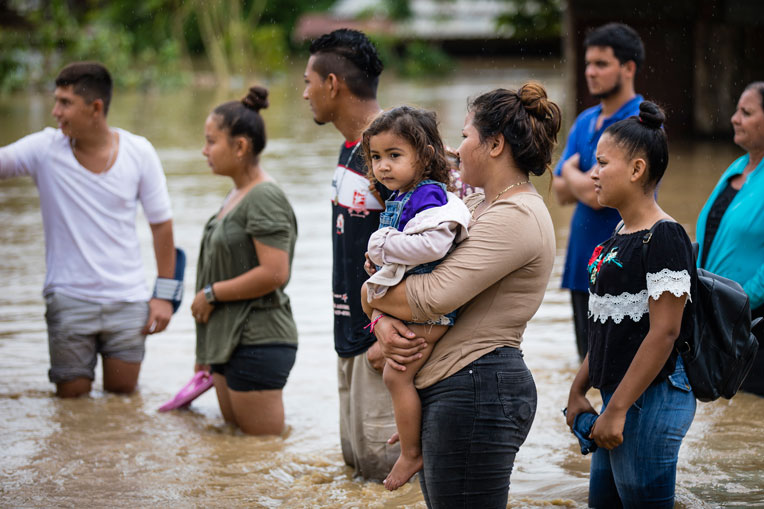 Families wade through floodwaters after Hurricane Iota.