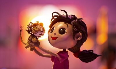 Lola's Lion film image: Girl holding a stuffed lion.