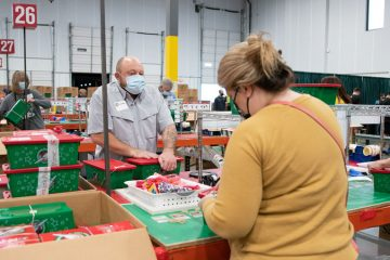 Marine Staff Sergeant Curtis and Jina Fowler help prepare shoeboxes for distribution.
