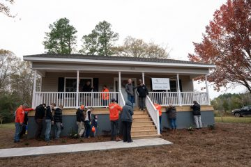Curtis Bradley, construction foreman on the project, leads prayer at the home with Michael, his family along with our staff and volunteers.