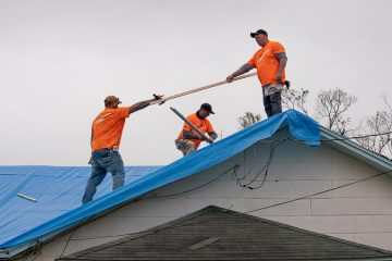 Volunteers tarp the Terry's damaged roof.