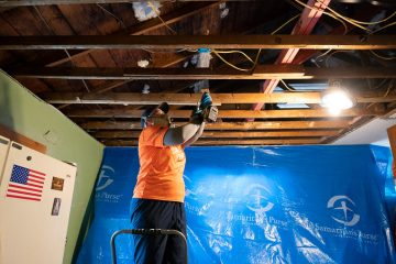 Pam Joaquin rips out a water-damaged ceiling in Rusty's home.