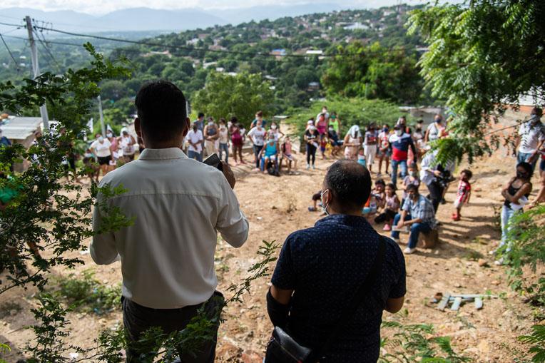 Pastor Yahir speaks to families before the Samaritan's Purse food distribution in Maria Auxiliadora.