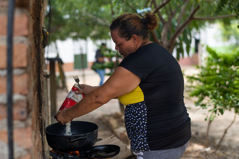 Alexandra prepares rice. She cooks not only for herself but for her family and several others in the community.