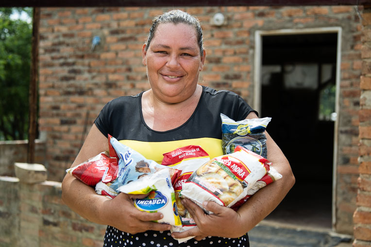 Alexandra stands with some of the food items she received in her basket from Samaritan's Purse.