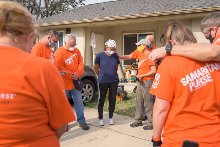 Samaritan's Purse volunteers pray with Netsi at the conclusion of their work on her home.
