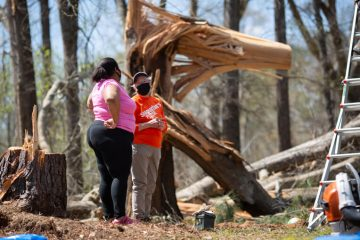 Danisha meets with a volunteer in the shadow of a twisted pine that damaged her Selma, Alabama, home.