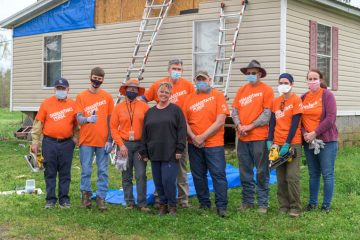 Tessa Sims joins the Samaritan's Purse volunteers to celebrate the work completed on her property.
