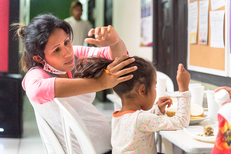 Maria put her daughter's hair in a ponytail at breakfast at our shelter in Bucaramanga.