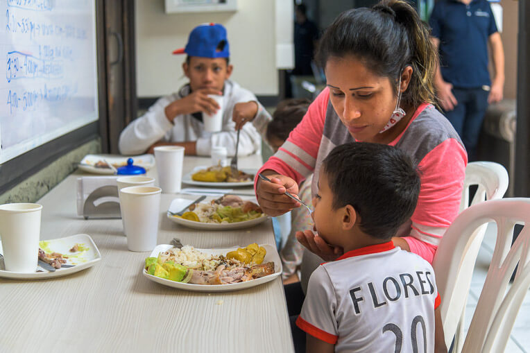 Maria, who recently fled Venezuela, helps feed one of her sons at lunchtime.