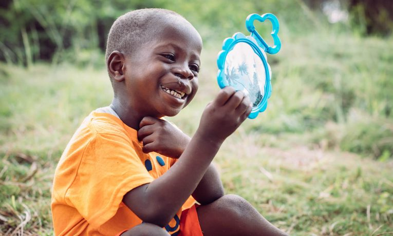Emmanuel has a hard time not looking at his miraculously new lip after cleft lip surgery at ELWA.