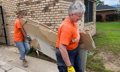 Volunteers work hard to remove damaged drywall.