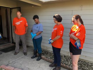 Volunteers take time to pray with Christine following work on her home.
