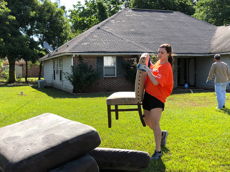 Volunteer Molly Jackson helps salvage furniture and other belongings from the flooded home.