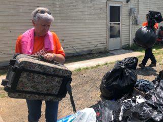 Volunteer Sarah Rutland helps carry ruined belongings from a flooded home.