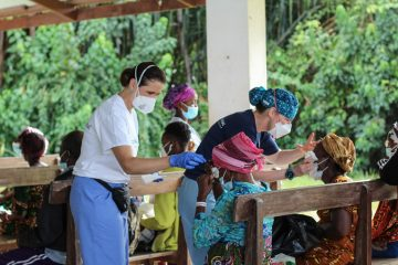 Our surgical team performs post-operative checks of patients in the shade of the hospital's chapel.