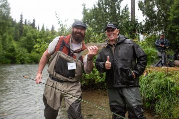 Air Force Master Sergeant Peter Stein holds an Arctic grayling while Vice President Mike Pence gives a thumbs up.