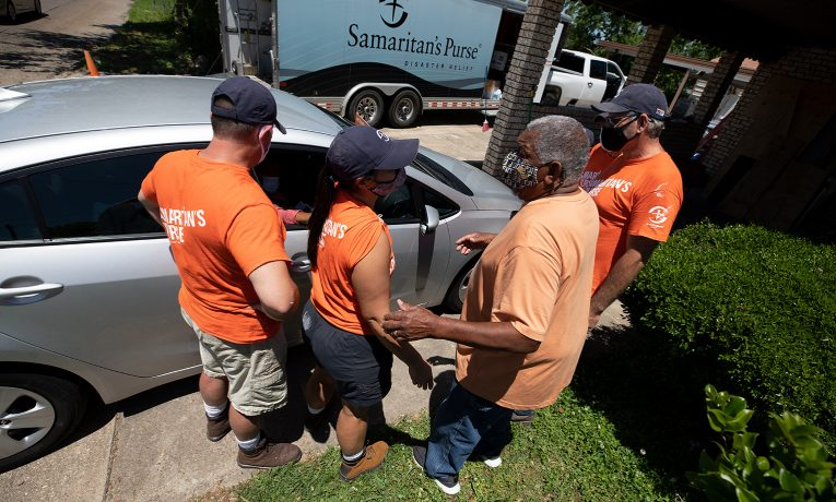 Homeowner Rufus Goodwin gathers with volunteers to pray outside his Lake Charles home.
