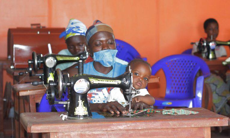 Una madre aprende a coser en nuestro lugar seguro en Bunia, mientras su niño pequeño la observa.