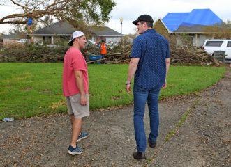 Edward Graham visits with homeowner Bradley Giroir in Houma.