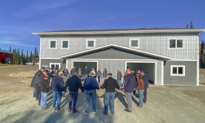 Staff, volunteers, and leaders from Amundsen Educational Center gather around the completed student housing to pray for future students and the school.
