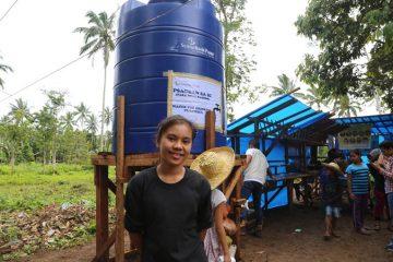 Aizah helps clean the potable water storage tank.